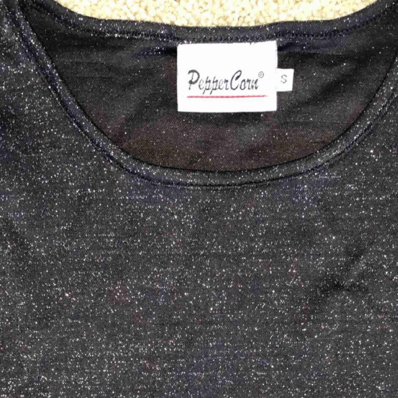 Väldigt snygg t-shirt som är svart glittrig. I bra skick. Har i princip aldrig använt, säljer i hopp om att någon annan kan få mer användning av den än jag.💖. T-shirts.