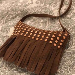 En liten väska med nitar och fransar som kan bäras hur man vill, men som jag själv har använt som crossover.  Storlek 16x11 (Kontakta mig för mer bilder)