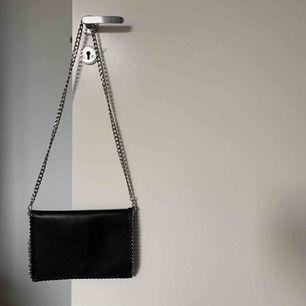 En svart & silvrig shoulder bag från Nelly Accessories. Sparsamt använd & i fint skick.   Stängs med en knapp & har en innerficka med litet dragkedjelåst fack.   Köparen står för frakten (samfraktar gärna!)