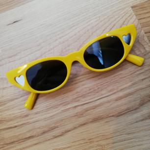 Gula coola solglasögon med svart glas och silvriga/spegelhjärtan på sidorna. Frakt 18 kr.