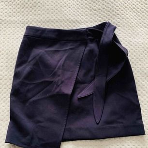 Mörkblå kjol från HM med knytning i midjan. Aldrig använd.