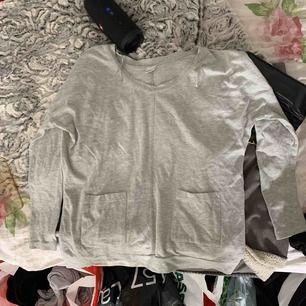 En fin vanlig grå tröja från Gina med två fickor där fram