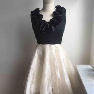 Supersöt knälång klänning som passar dig som klär dig i XS-S. Klänningens kjol är i organzamaterial. Blixtlås finns på baksidan av klänningen. Aldrig använd, prislappen sitter kvar.