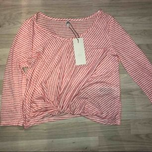 En röd/vit randig tröja, aldrig använd då den var för liten!
