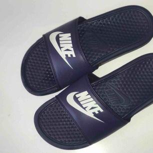 Ett par marinblå Nike tofflor. Har använts som inneskor, därför inte så slitna. Säljs för 150kr. Betalning sker via swisch :)) köparen står för frakt