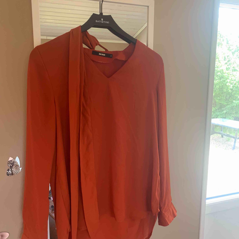 En orange/röd blus från bik bok, inte använd. Finns ett snöre du kan välja att knyta eller inte, fint tilläg.😊. Skjortor.
