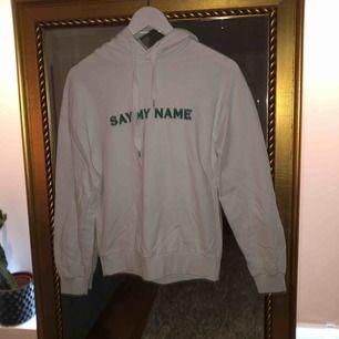 """Vit hoodie med grön text """"say my name"""". Frakten är 54!"""