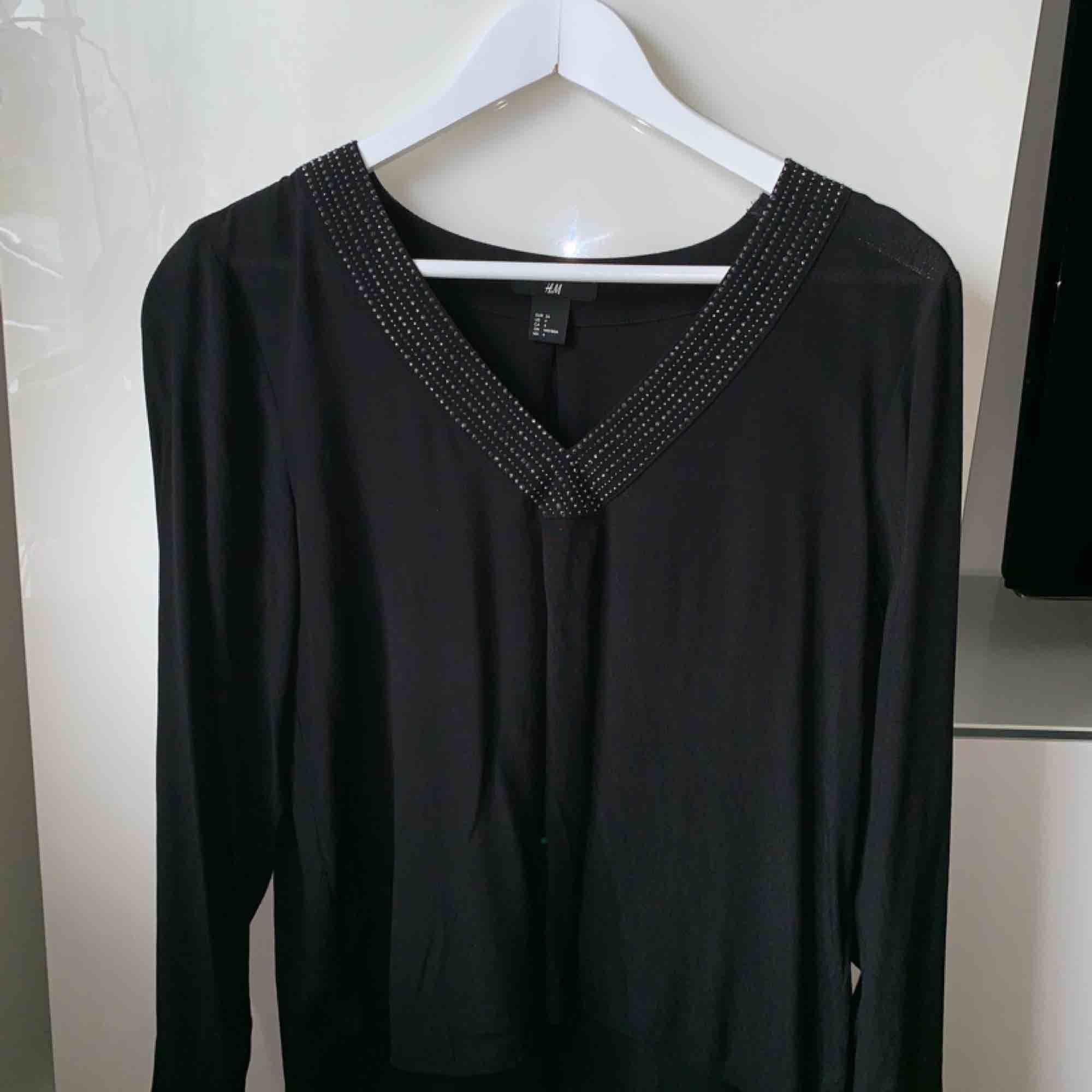 Svart långärmad tröja med v-ringning. Lite längre baktill än framtill & har svarta/silvriga stenar runt v-ringningen. Frakt ingår!. Toppar.