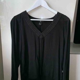 Svart långärmad tröja med v-ringning. Lite längre baktill än framtill & har svarta/silvriga stenar runt v-ringningen. Frakt ingår!