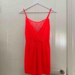 Neonrosa (ser mer röd ut på bild men är rosa) playsuit från H&M. Reglerbaraband, urringning i ryggen, korsad framtill med spets-detalj! Frakt ingår!