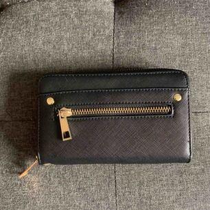 Svart plånbok med guldiga detaljer i mycket fint skick. Många rymliga och användbara fack för kort, kontanter, kvitton m.m.   Köparen står för frakten (25kr)💕  Kontakta gärna vid intresse! ✨