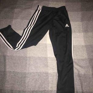 Ett par adidas byxor i stl 140, 9-10 years old. 3 streck på sidorna och har snören på insidan av midjan.