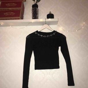 En tunn och ribbad svart tröja med diamanter i kragen. Använd några få gånger.