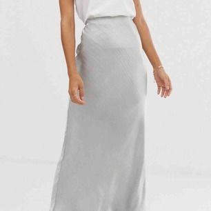 Silvrig silkig kjol från Asos i storlek 16/XL. Resår i midjan så den kan passa både större och mindre. Använd 1 gång.