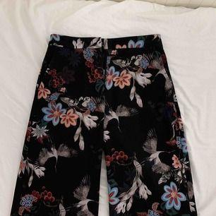 sjukt fina byxor från H&M! Använt mycket men i bra skick. Svarta byxor med färgglatt mönster och lite vidare ben. Sitter så snyggt på kroppen. Köpare står för frakt ✨