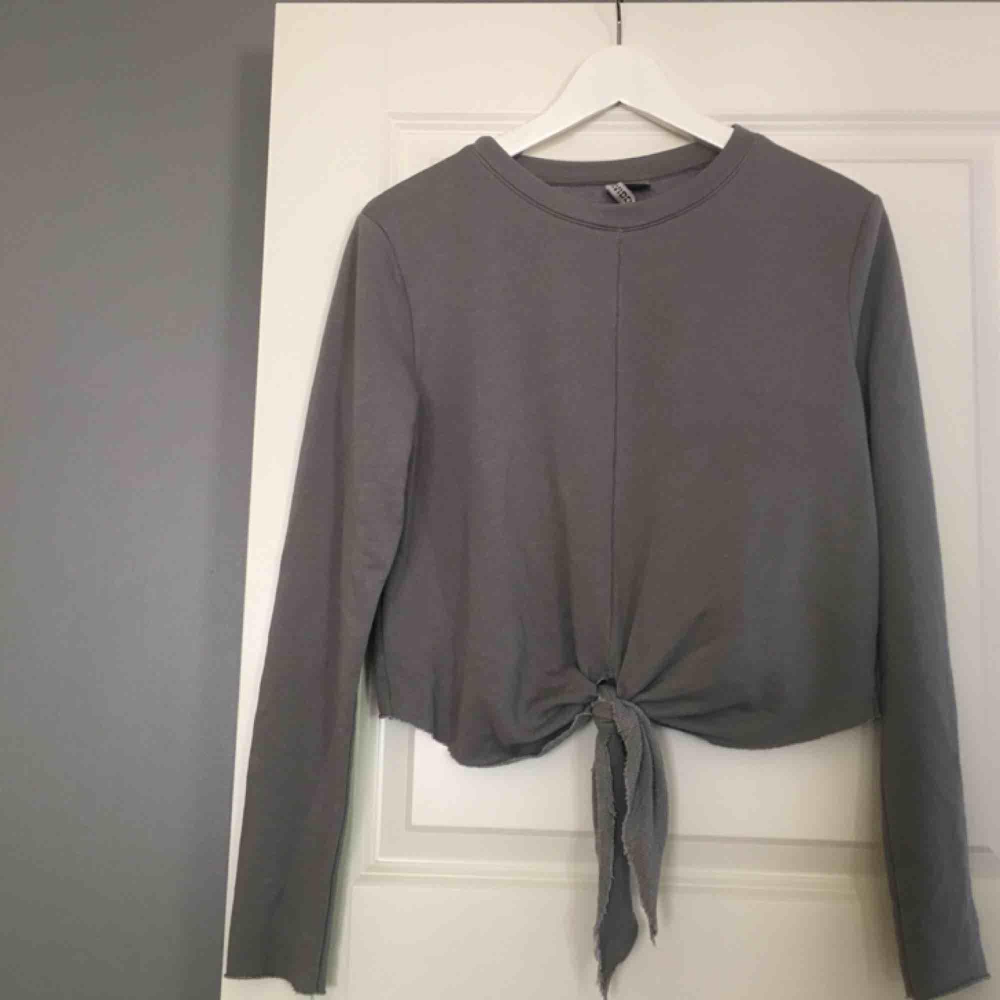 En långärmad, grå tröja med knyt i fram. Väldigt enkel, men väldigt snygg och enkel att styla. Köparen står för frakten! . Toppar.