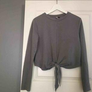 En långärmad, grå tröja med knyt i fram. Väldigt enkel, men väldigt snygg och enkel att styla. Köparen står för frakten!