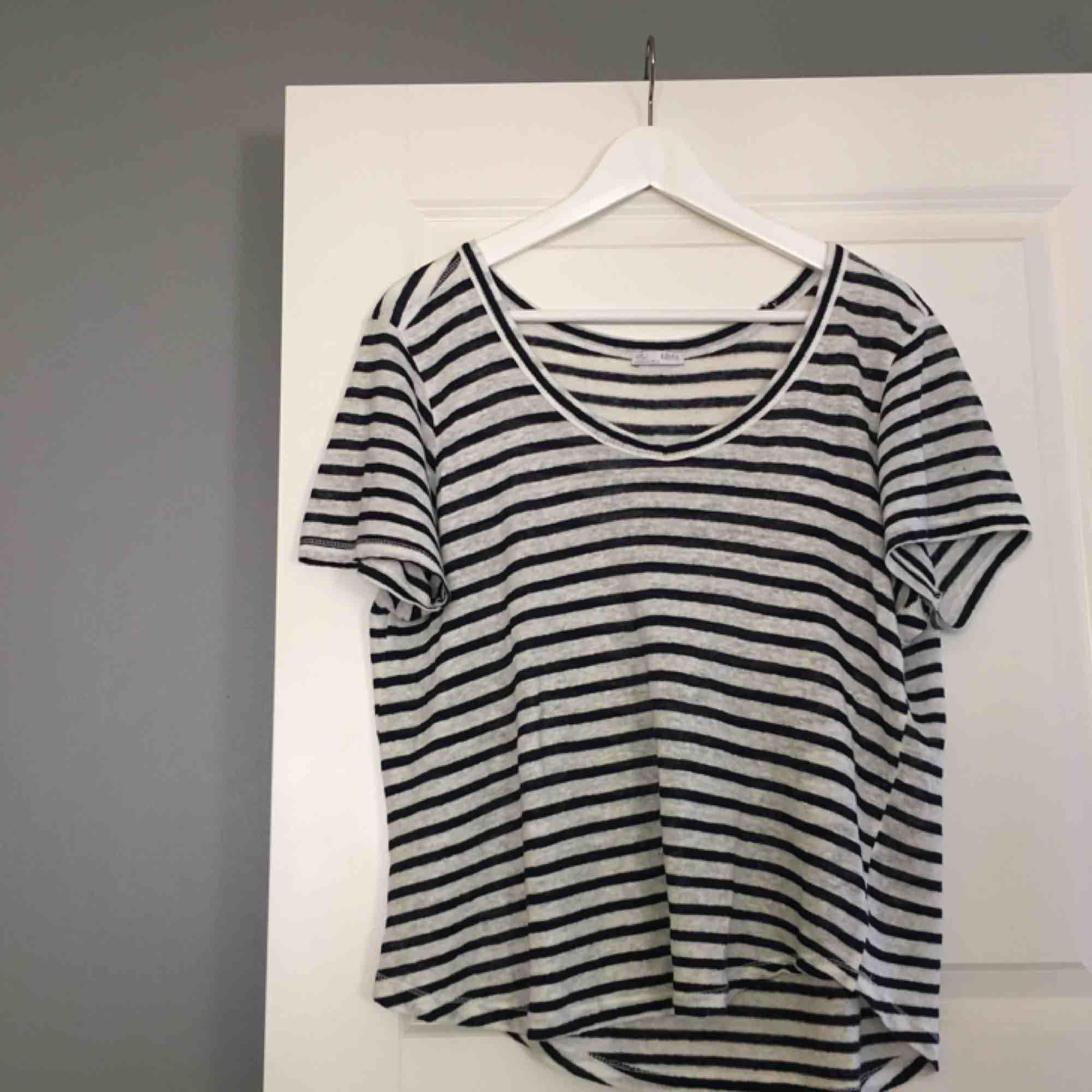 En enkel T-shirt i blåvitt randigt mönster. T-shirten är i nyskick eftersom den aldrig är använd. Köparen står för frakten! . T-shirts.