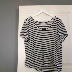 En enkel T-shirt i blåvitt randigt mönster. T-shirten är i nyskick eftersom den aldrig är använd. Köparen står för frakten!