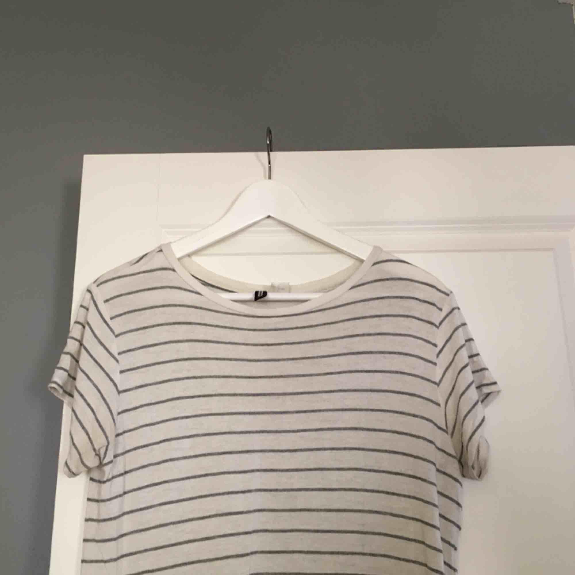 En lång T-shirt från HM med en snygg slits i midjan. Fint randigt material i fint skick. Köparen står för frakten! . T-shirts.