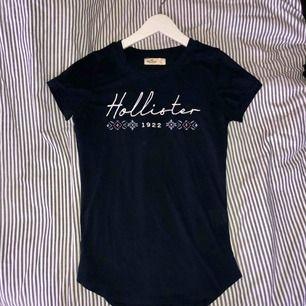 FRAKT: 18kr T-shirt med broderad hollister text. Bra skick, lite smått noppig. Stl.xs men plagget är strechigt så skulle nog sitta bra på en xs/s. KÖPAREN STÅR FÖR FRAKTEN.  Swisch är det som gäller. Priset kan diskuteras ;)