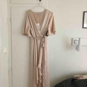 Satin Wrap Dress, från Nelly. Färgen heter Champange men går mer åt det rosa hållet. Kortare framtill, längre bak! Aldrig använd!