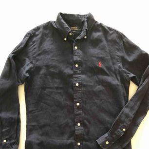 Mörkblå linneskjorta från RL i slim fit. Skjortan är använd ett fåtal gånger och är i nyskick. Hämtas i Malmö eller skickas mot frakt.
