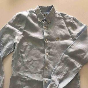 Ljusblå linneskjorta i slimfit. Använd endast en gång och är i nyskick.