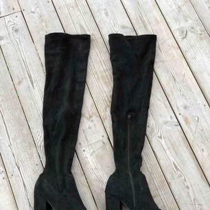 Svarta overknee boots i storlek 40. Knappt använda men tyvärr har det blivit två små hål (se bilder) i övrigt är dom i väldigt fint skick. Kan skickas, köparen står för frakten. Hämtas i Onsala.