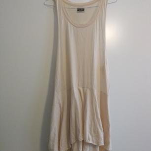 strl M, lös klänning i svagt off-white/rosa. Kan bäras av S och L tack vare den hängande passformen.