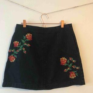 Svart jeanskjol med röda broderade blommor på framsidan och dragkedja där bak från Topshop. Kjolen är i storlek 38 men skulle säga att den passar storlek 40 också. Knappt använd och i jättefint skick. 💞 Köparen står för frakt.
