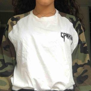 Vit långärmad tröja med camouflageärmar. Står i storleken M men funkar även om man har storlek S, då den blir lite oversized. Köparen står för frakt, Annars kan jag mötas upp i Stockholm