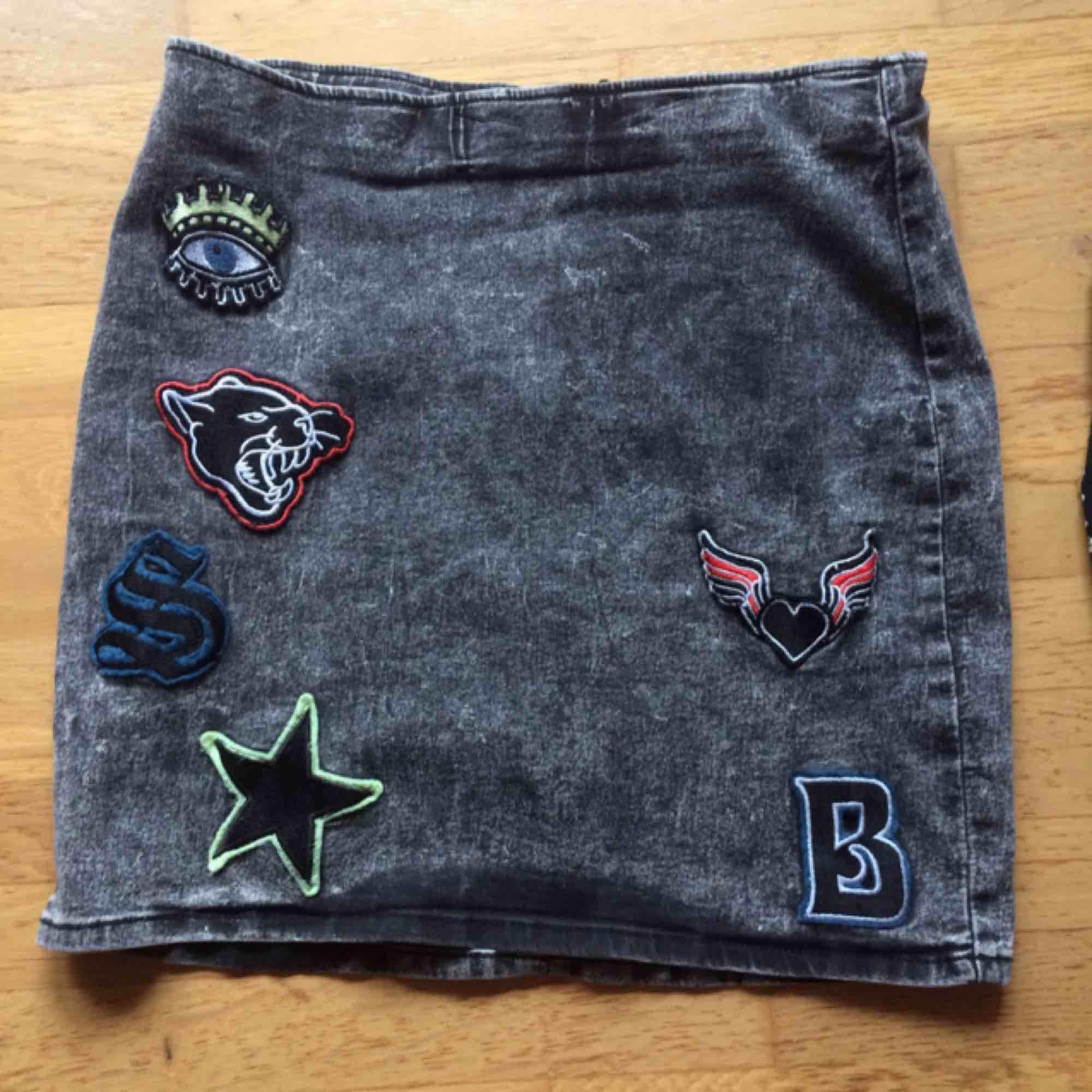 Oanvänd jeanskjol med patches i storlek 42. Frakt tillkommer med 42 kr i postens påse 🌸. Kjolar.