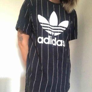 Längre baseball inspirerad t-shirt från Adidas. Mörkblå med vita ränder. Kan använda som klänning eller som en längre t-shirt. Fint skick, knappt använd.