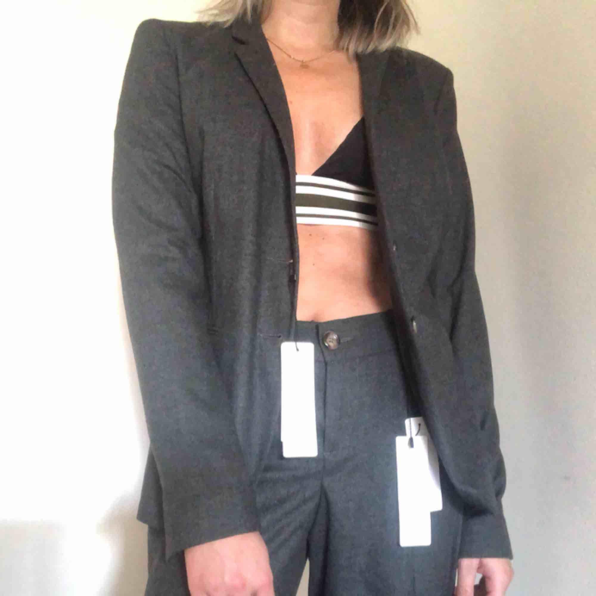 """Kostym (kavaj och byxor) i mjukt """"filttyg"""". Aldrig använd, lapparna kvar. Kavaj (1599kr ny) och raka kostymbyxor (899kr nya). . Kostymer."""