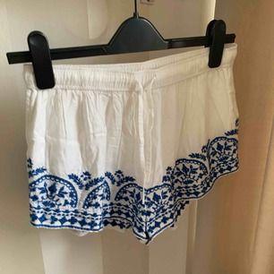 Vita shorts med blå broderade detaljer ifrån Gina Tricot! Använda väldigt få gånger och är i fint skick.  Säljer pga hinner inte använda dom.