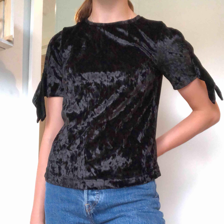 """En t-shirt/blus i sammetslikanande material. Den är knappt använd och i fint skick. På axlarna är det hål och två """"band"""" som hänger ner. Säljes i Göteborg!💞. Blusar."""
