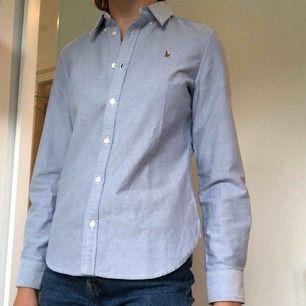 En Ralph Lauren skjorta i ljusblått med lite rosa och vitrandiga detaljer på sidan i kragen och innanför slutet på ärmarna. Skjortan är köpt i USA i Ralph Laurenbutiken och är i gott skick. Säljes i Göteborg