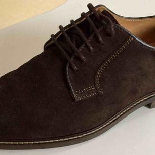GANT Ricardo Coffee Brown, storlek 41.   Finskor i mörkbrun mocka i stilren design. Skinnfodrad och med innersula i skinn, snygg och bekväm liten klack.   ALDRIG använda men höger sko har en liten skada som du kan se på bild 3.   Nypris 1600kr