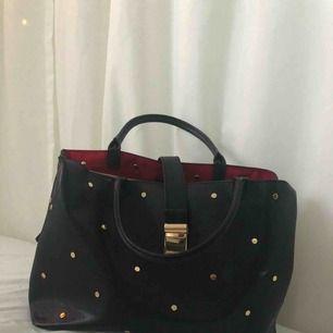 En svart handväska från h&m med gulddetaljer och tre individuella fack
