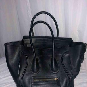 En svart rymlig handväska. En kopia på Céline luggage tote väska.