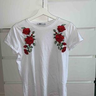 Vit T-shirt med blommor på. Använd 2 gånger och ser ut precis som när jag köpte den