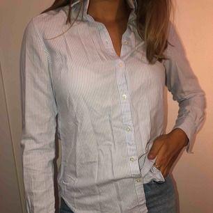 En fin ljusblå randig skjorta från GinaTricot. Köpt för flera år sedan men knappt använd. Passar även en 36.  Köparen står för frakten!