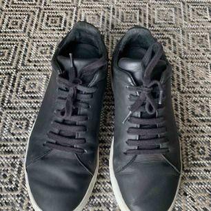 Axel Arigato sneakers i mattsvart skinn med lite högre sula. Storlek 38. Använda sparsamt!  Kan mötas upp i Göteborg, annars står köparen för frakten.