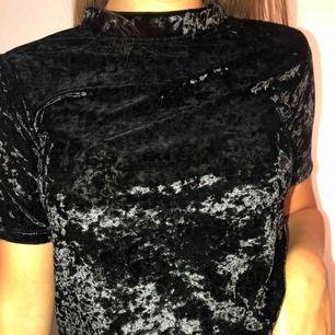 Svart sammets T-shirt med högre krage. Inte riktigt säker på vart den är köpt. I väldigt fin skick. Passar både till fest och till vardags.   Köparen står för frakten!