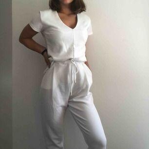 Jättefin, vit jumpsuit med fickor och knytning vid midjan.