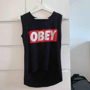Vanligt svart Obey linne som aldrig har använts. Lång bak