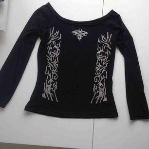 Tajt svart tröja med öppna axlar och tribaler! Använd endast ett fåtal gånger, stretchy material.