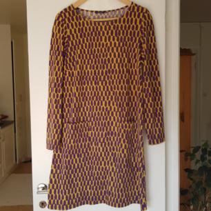 Lila-gul mönstrad klänning från Marimekko. Fickor på framsidan. Kan mötas i Uppsala, eller så står köparen för frakt.