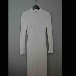 Vit paljett klänning, öppen rygg och axelkuddar  Väldigt stretchig, passar alla kroppsfigurer från  36-40!  Aldrig använd!!